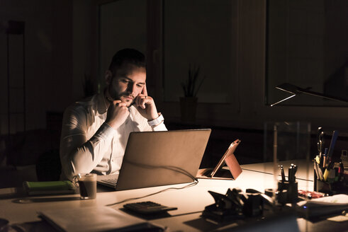 Pensive businessman working on laptop in office at night - UUF13198