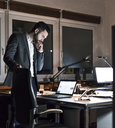 Businessman standing in office at night looking at laptop - UUF13201