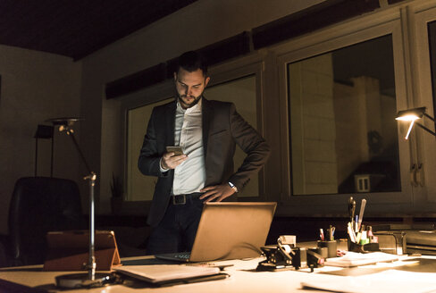 Businessman standing in office at night using smartphone - UUF13204