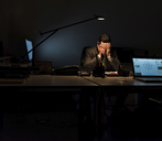 Overstressed businessman sitting at his desk in the dark - UUF13207