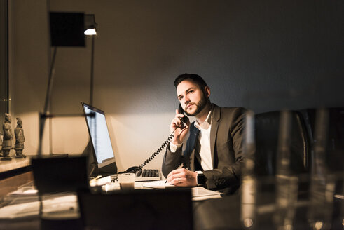 Businessman on the phone in office at night - UUF13210
