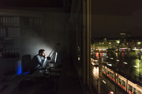 Businessman working on computer in office at night - UUF13213