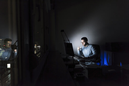 Businessman with cup of coffee working on computer in office at night - UUF13216