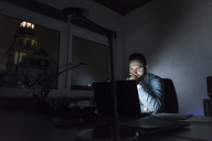 Businessman working on laptop in office at night - UUF13219