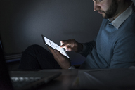 Businessman working on tablet in office at night - UUF13225