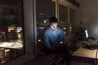 Businessman sitting on window sill in office at night using tablet - UUF13231