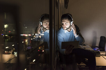 Businessman sitting on window sill in office at night listening music with headphones - UUF13234