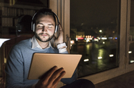 Businessman sitting on window sill in office at night listening music with headphones and tablet - UUF13237