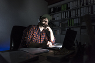 Portrait of freelancer sitting at desk at night using laptop and headphones - UUF13246