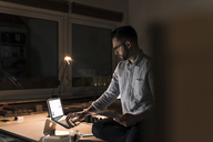 Businessman working late in office - UUF13249