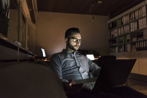 Businessman working on laptop in office at night - UUF13252