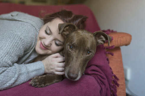 Portrait of dog lying with owner on the couch at home - JASF01854