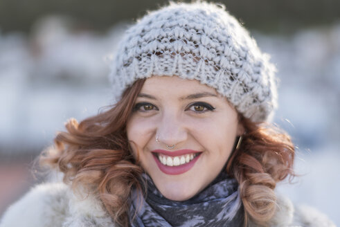 Portrait of laughing young woman with curly hair wearing wool cap and nose piercing - JASF01866