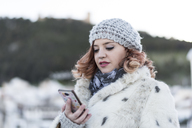 Portrait of young woman looking at cell phone in winter - JASF01869