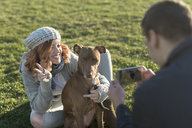 Man taking picture of his girlfriend and the dog on a meadow - JASF01875