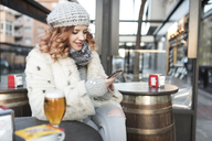 Young woman using cell phone on terrace of a pub in winter - JASF01881