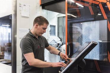 Man operating machine in factory - DIGF03661