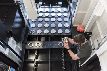 Man examining workpiece in factory - DIGF03676