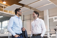 Two smiling businessmen talking in modern factory - DIGF03697