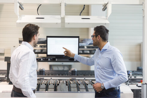 Two businessmen talking at screen in modern factory - DIGF03700