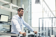 Businessman standing at railing in factory thinking - DIGF03706