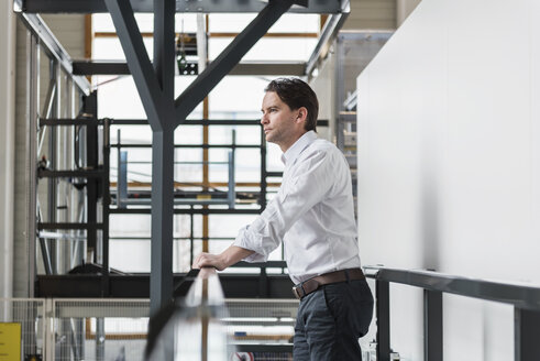 Businessman standing at railing in factory thinking - DIGF03709