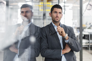 Businessman leaning against glass pane in modern factory thinking - DIGF03718