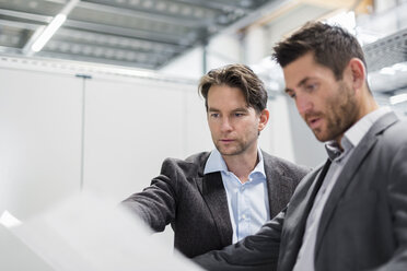 Two businessmen looking at plan in modern factory - DIGF03727