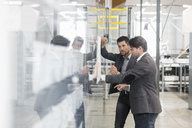 Two businessmen looking at plan in modern factory - DIGF03730