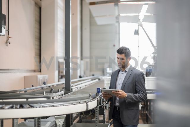 Businessman using tablet at conveyor belt in factory - DIGF03733