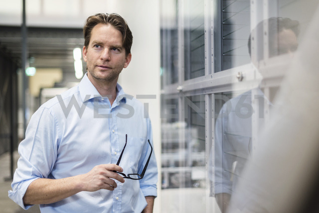 Portrait of confident businessman in a factory - DIGF03742