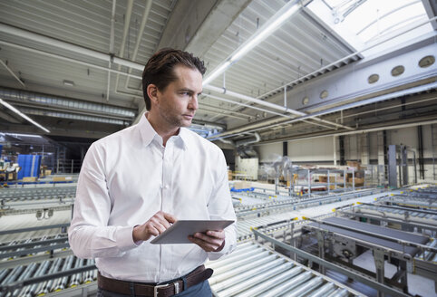 Businessman using tablet on factory shop floor - DIGF03753