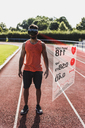 Athlete on tartan track wearing VR glasses surrounded by data - UUF13255