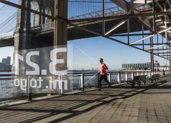USA, New York City, man running at East River with data emerging from smartwatch - UUF13261