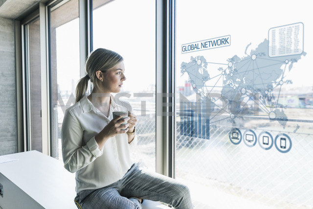 Young businesswoman looking at virtual world map at window pane in office - UUF13264 - Uwe Umstätter/Westend61