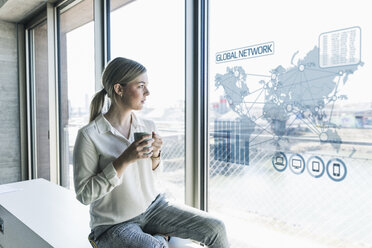 Young businesswoman looking at virtual world map at window pane in office - UUF13264
