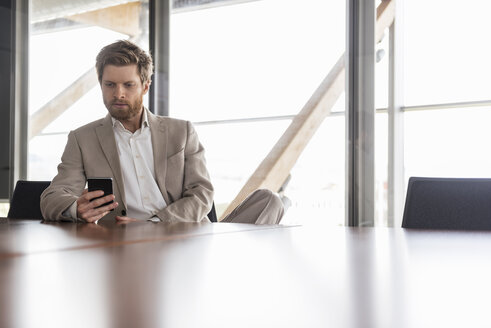 Businessman using cell phone in conference room - DIGF03761