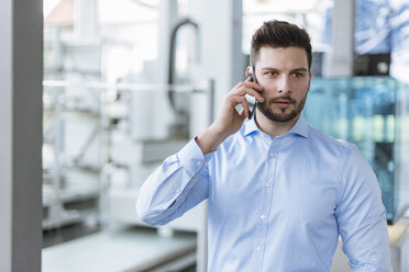 Portrait of man on cell phone in factory - DIGF03791