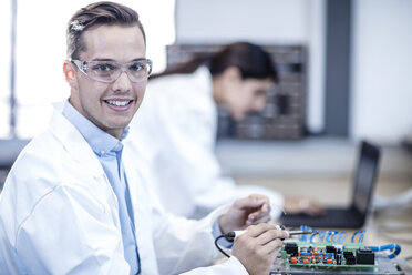 Portrait of smiling technician working on motherboard - ZEF15273