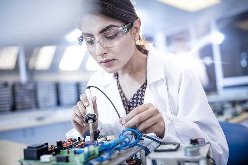 Female technician working on motherboard - ZEF15276