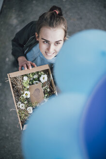 Portrait of smiling woman with present in cardboard box and blue balloons looking up - GUSF00613