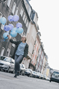 Happy woman with blue balloons walking on the street - GUSF00616