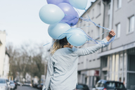 Back view of woman with blue balloons - GUSF00619