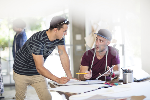 Two fashion designers talking and taking notes in studio - ZEF15303 - zerocreatives/Westend61