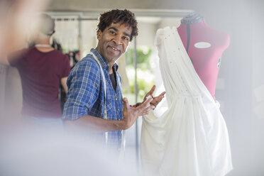 Smiling fashion designer presenting dress - ZEF15312