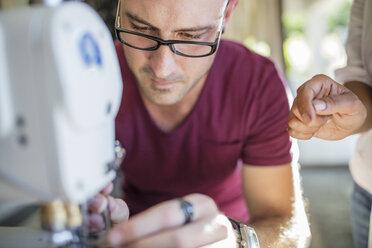 Close-up of man using sewing machine - ZEF15321