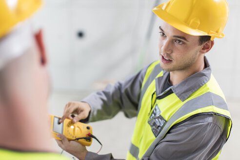 Electricians working with voltmeter on construction site - ZEF15342
