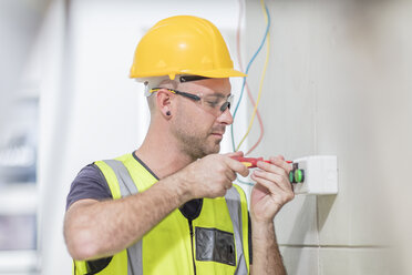 Electrician screwing in wire on construction site - ZEF15348