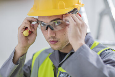 Electrician putting on protective glasses - ZEF15351