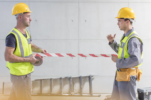 Construction workers using tape on construction site - ZEF15366